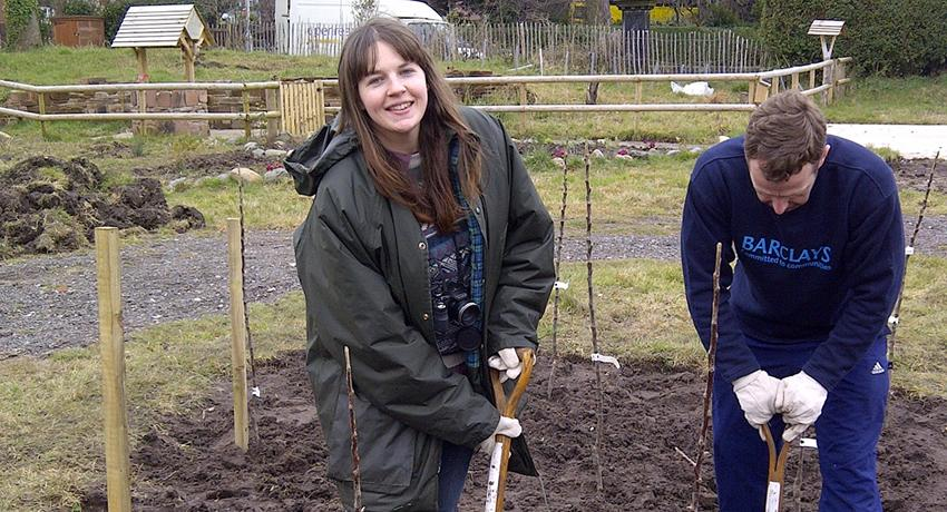Sarah from Fruit Routes digs with a Barclays CSR volunteer at the Fruit Routes EKG orchard
